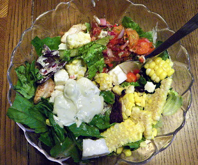 Partially eaten salad with additional scoop of dressing