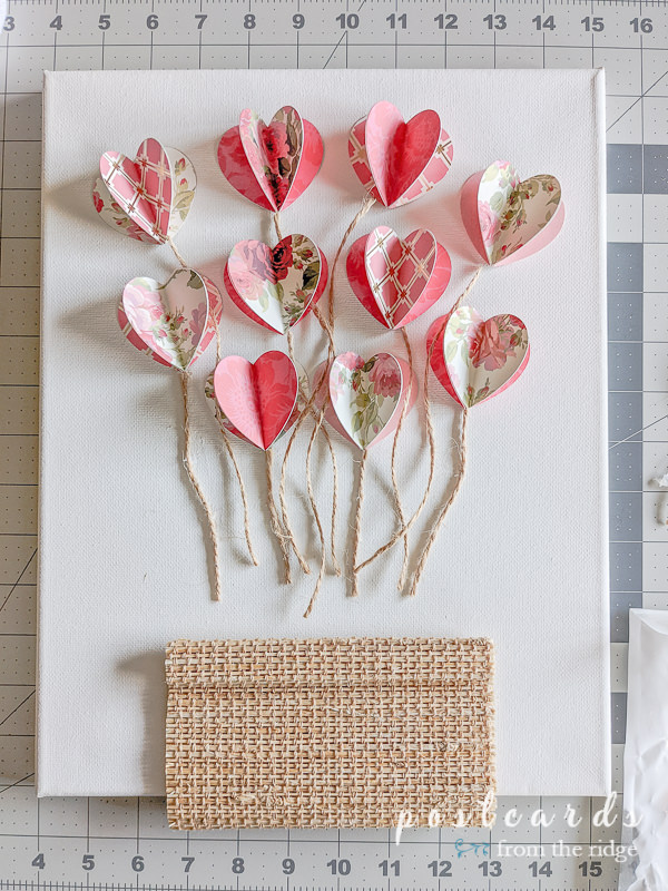 pieces of twine and 3-d paper hearts on white canvas