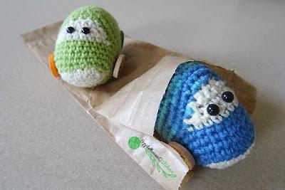Niebieskie aukto wykonane na szydełku wystaje z papierowej torebki, w którą został zapakowany. Z tyłu, na torebce leży zielony samochodzik również wykonany na szydełku.