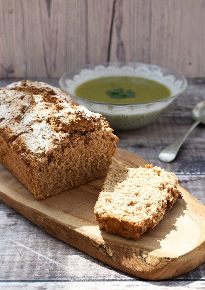 Wholemeal beer bread loaf with a slice cut on a wooden board next to a  bowl of broccoli soup