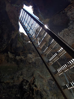 Underneath a metal stair ladder looking up to the top of the ladder at a cave opening