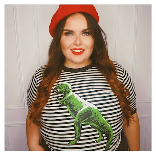 Plus size woman with long brown hair wearing dinosaur top and red beret