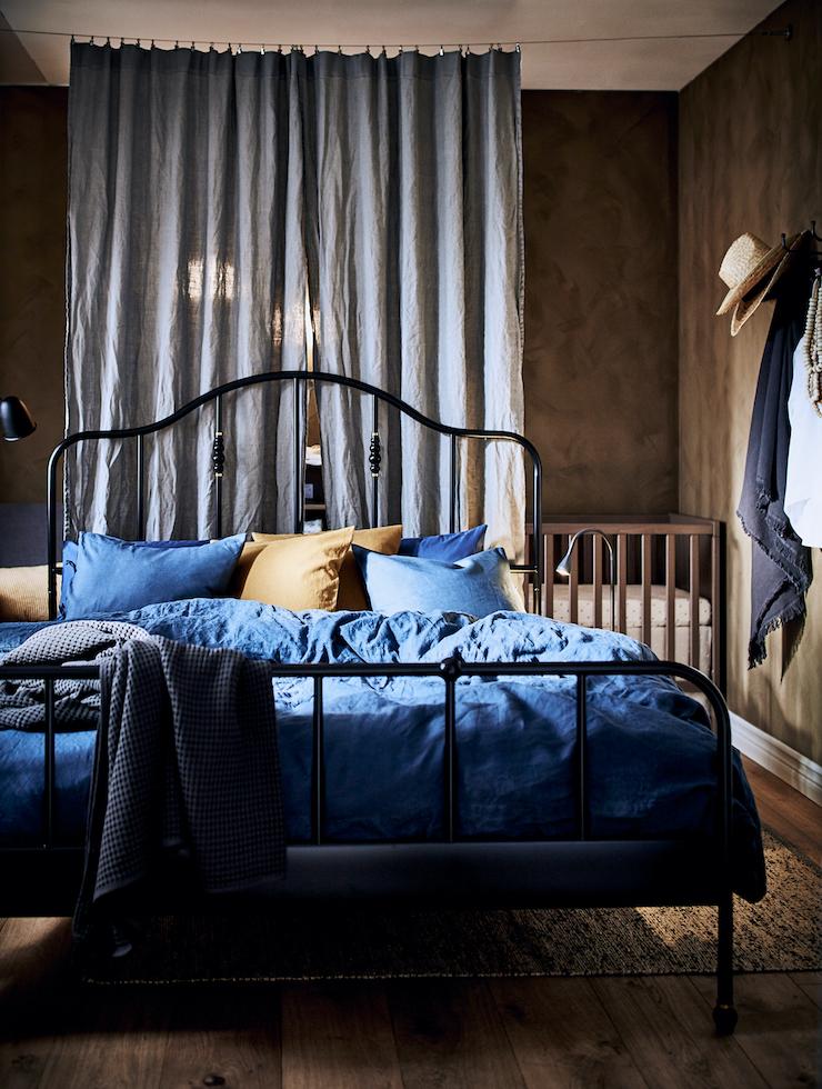 Nuevo catálogo IKEA 2021 dormitorios: dormitorio con cama de forja negra y ropa de cama en azul.