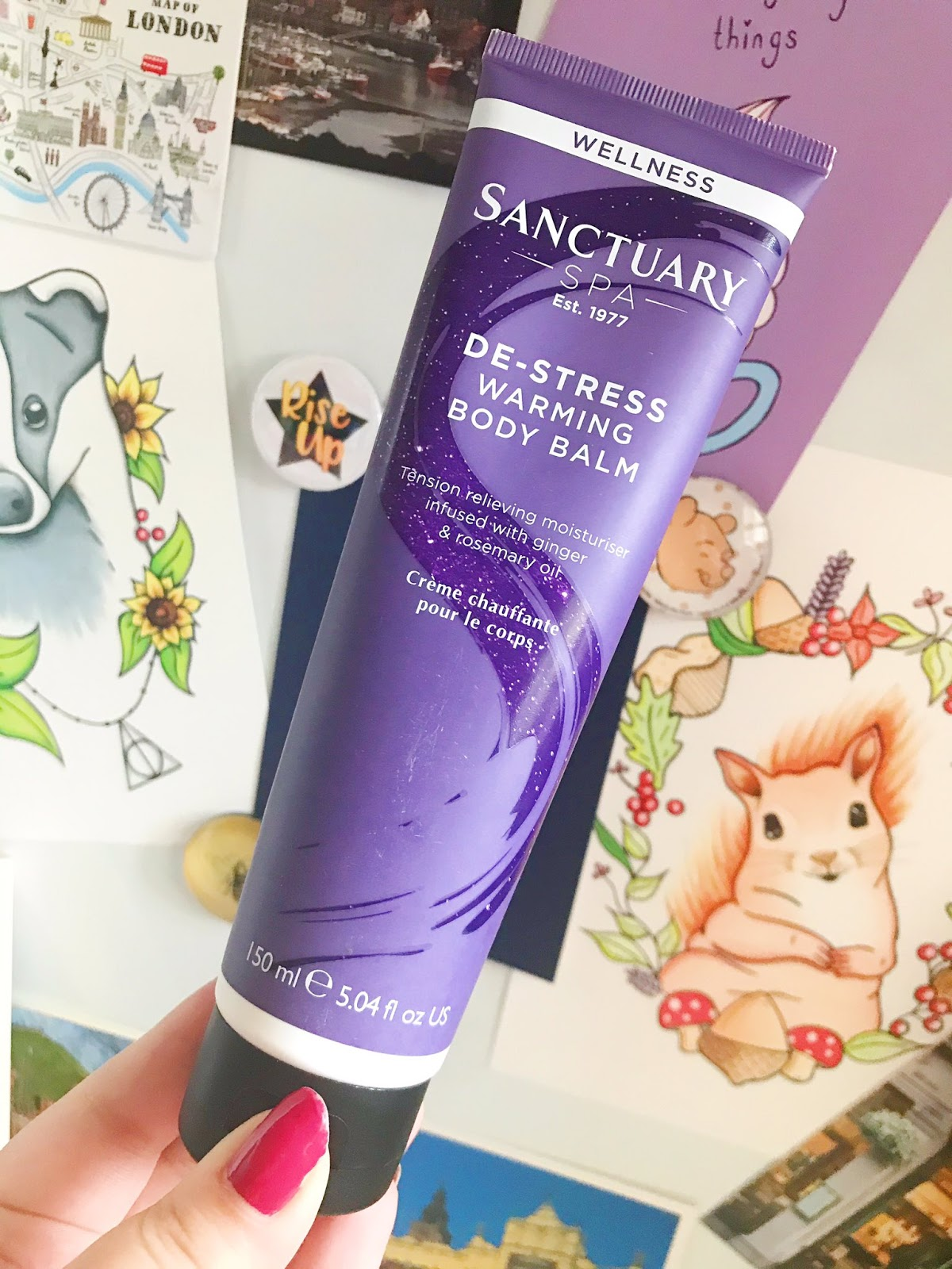 Sanctuary Spa De-Stress Warming Gel held up in front of prints on desk