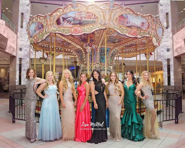 Group of teen girls in prom dresses in front of carousel