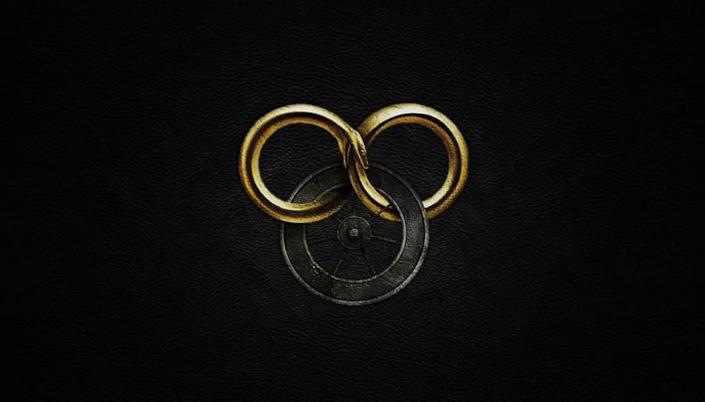 Fundo é preto e no centro tem três círculos que estão interseccionados entre si. O de baixo é uma roda metálica com aros e os dois círculos de cima é uma cobra enrolada no próprio rabo formando um símbolo de infinito na cor dourada.