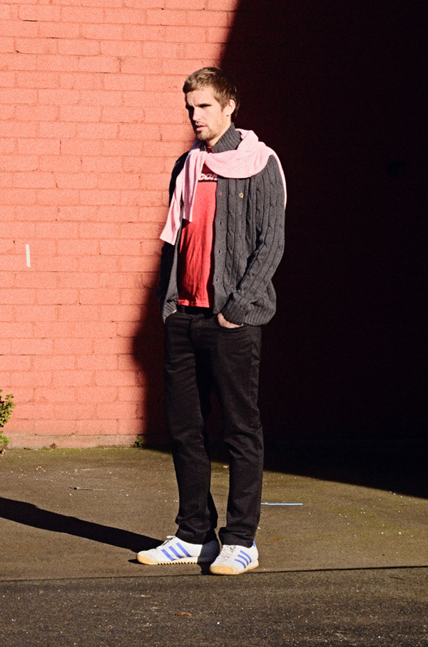Rapture in Sydenham, Shot 5, MERC Pyland Pink Knit Jumper &  Sneath Charcoal Knit button front Cardigan. Thrift shop 'new' Red SAUCONY Tee, pants & Shoes same as shot 3. Brown Wall D_600-D_5290