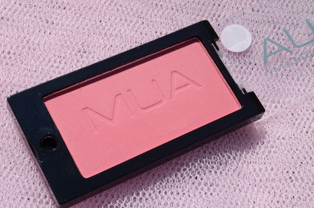 Image of the powder blush with the lid opened revealing the pan and engraved detailing in the powder