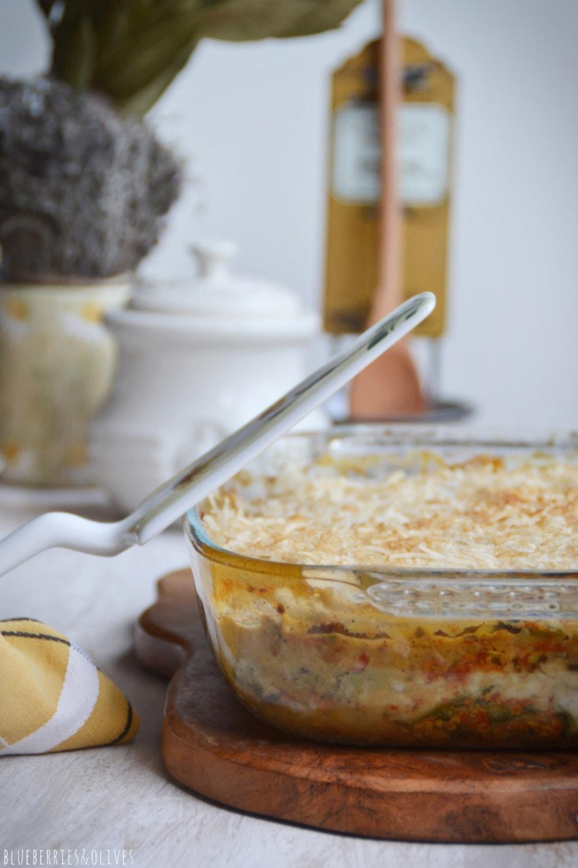 Lasaña de berenjenas en fuente de cristal sobre tabla de madera, con ingredientes de fondo, hierbas aromáticas, laurel seco,