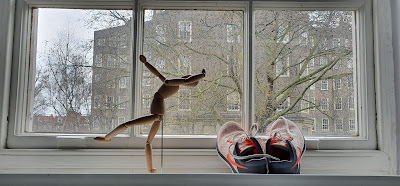 A pair of running shoes sits beside a poseable wooden figurine in a dramatic pose on a windowsill.
