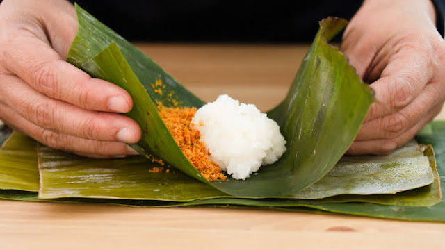 Making envelope containing fish floss to sticky rice on banana leaves photo