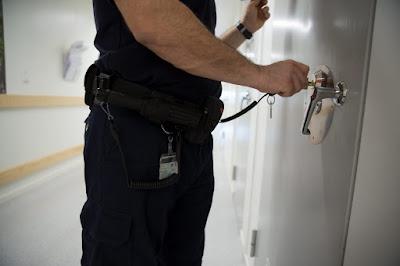 Häktesvakt som låser eller låser upp en häktesdörr.