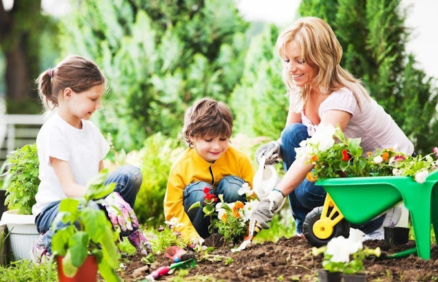 A mother with her two children tending to the garden