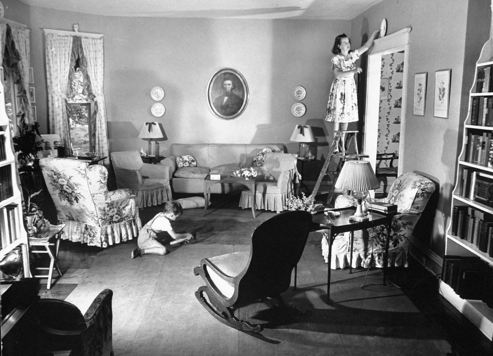 Jane standing on ladder to place special china plate as decoration above the doorway in the living room, which she decorated herself, as her son Tony plays on the floor.