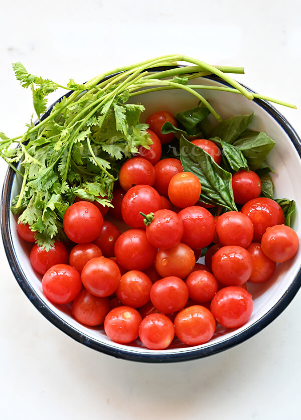 a plate with cherry tomatoes basil leaves and cilantro