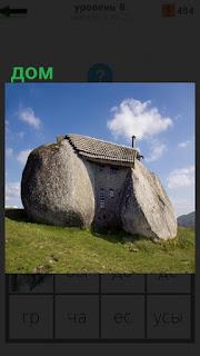 На зеленом холме стоит дом, который сделан из двух больших камней