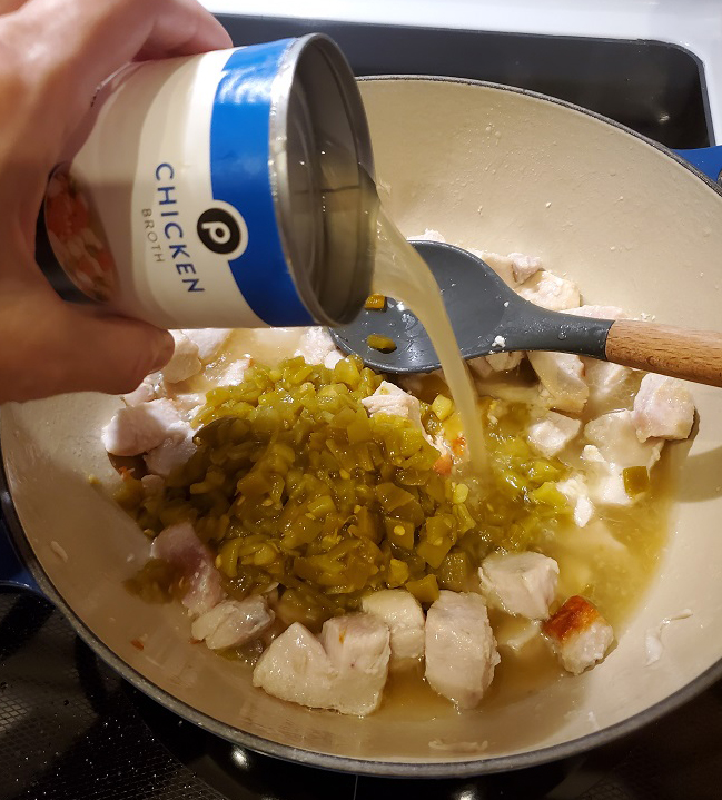 this is a photo of le creuset pan with chicken broth and chicken to make chicken chili