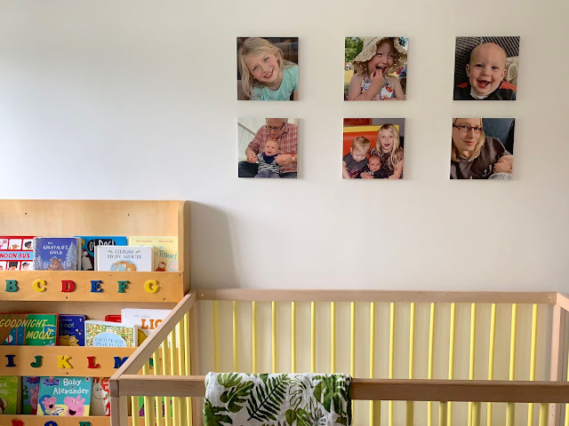 MIXPIX photo tiles up on the wall in a nursery with a bookshelf and cot visible