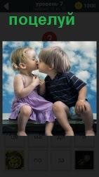 Двое маленьких детей совершают поцелуй под открытым небом в солнечную погоду