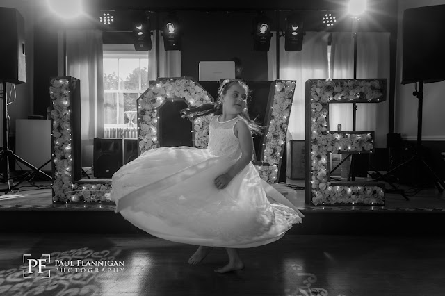 black and white photo flowergirl dancing at wedding