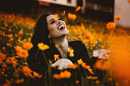 A joyful and happy person lying in a field of beautiful yellow flowers