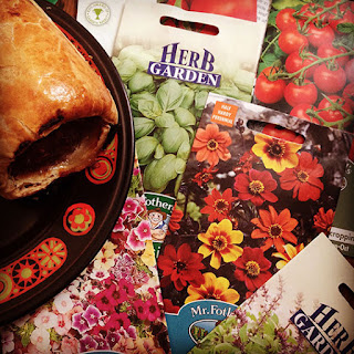 a pile of Fothergill's seed packets, and a sausage roll on a retro plate