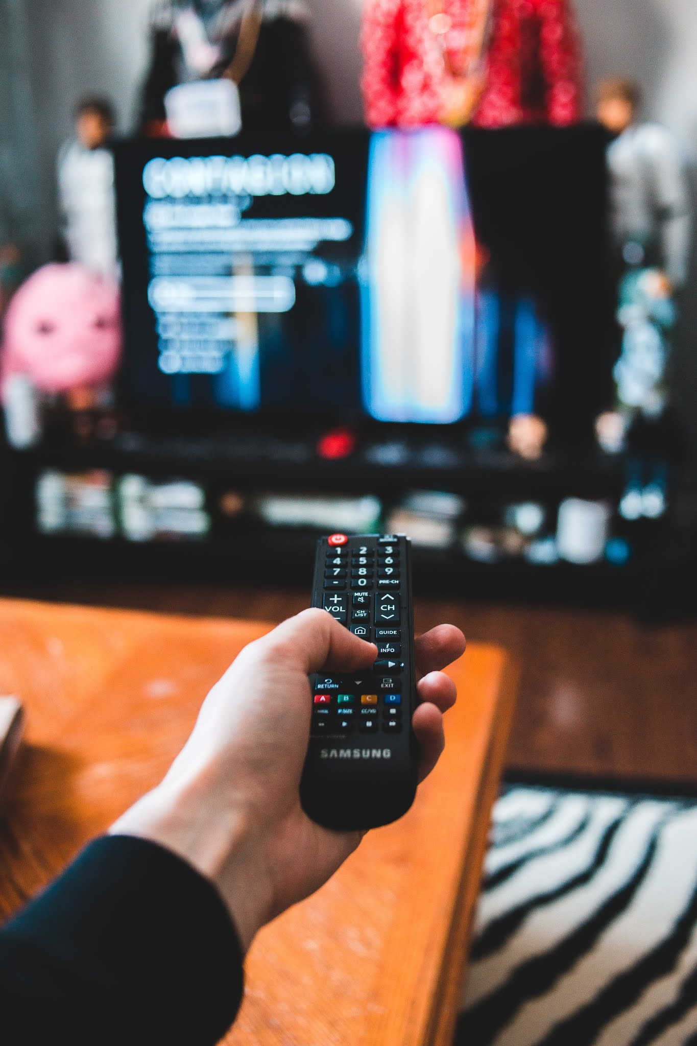 person holding black remote control watching netflix