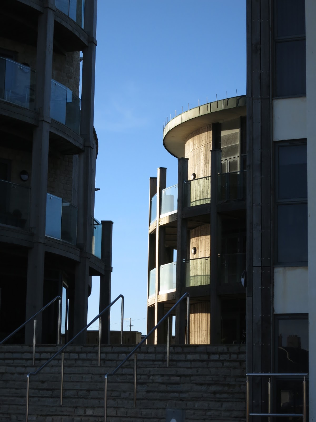 Curved buildings with steps between and blue sky beyond.