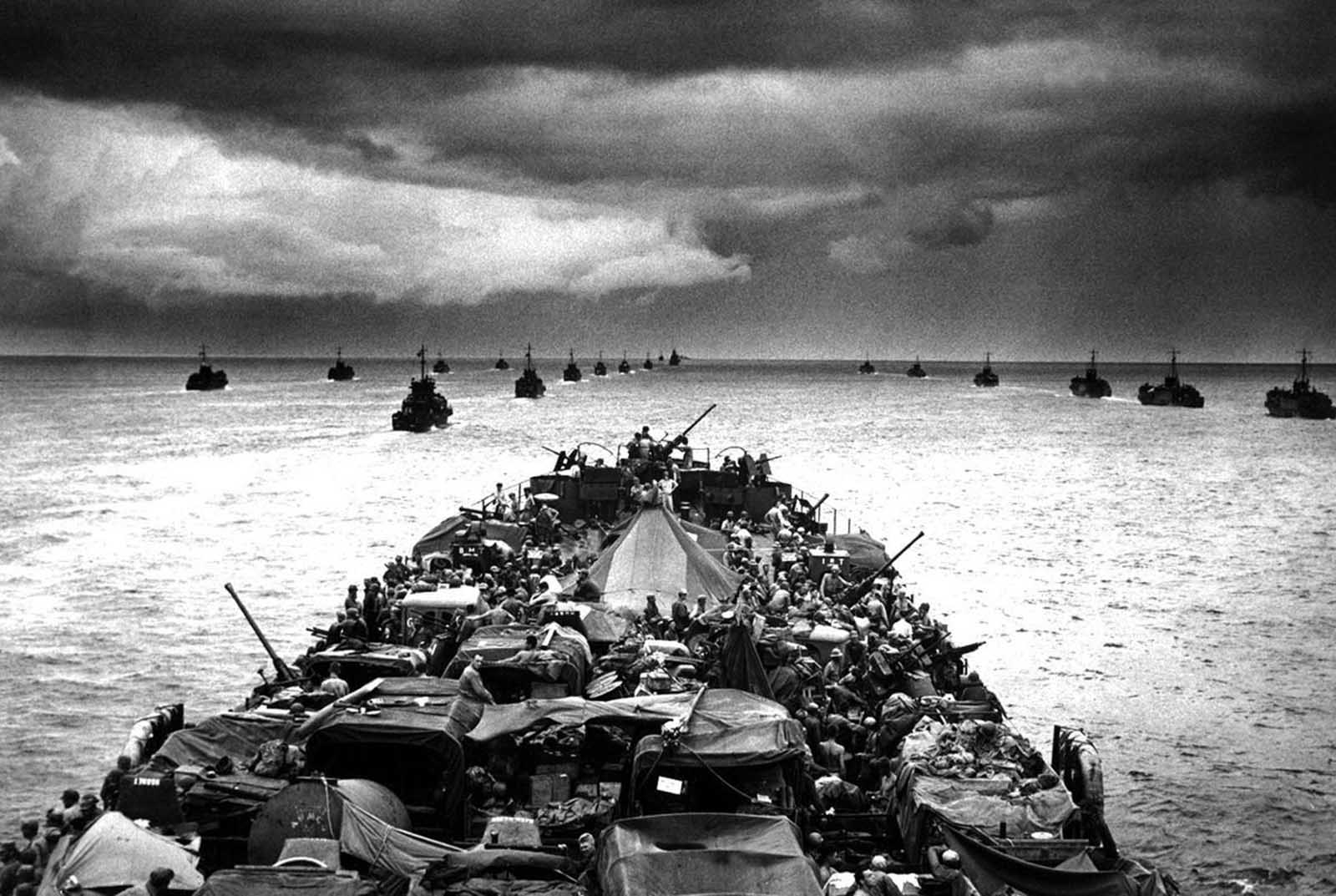 Columns of troop-packed LCIs (Landing Craft, Infantry) trail in the wake of a Coast Guard-manned LST (Landing Ship, Tank) en route to the invasion of Cape Sansapor, New Guinea in 1944.