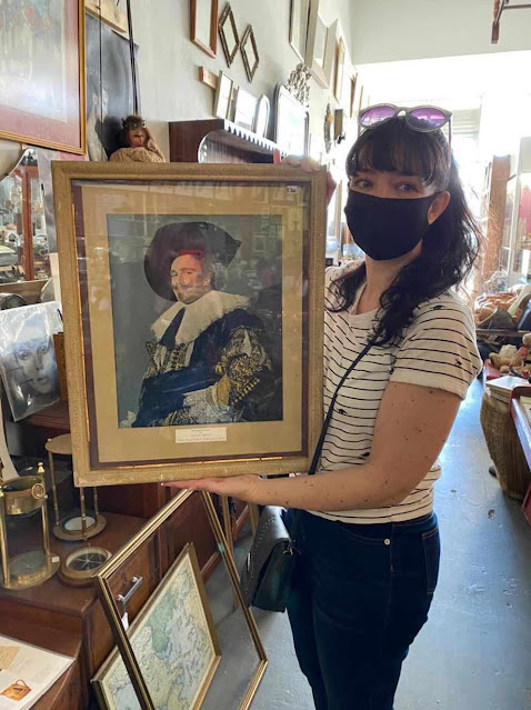 A shopper holds up her purchase at an antique shop in Cape Town