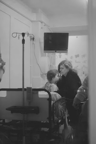 Black and white photo of Steph lifting Daisy out of a hospital bed taken from the door of the room