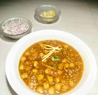 Serving garnished chole(chickpeas) with chopped onion and lemon wedges for chole recipe
