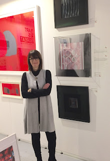 Gill smiling and standing in front of some of her prints mounted on a wall
