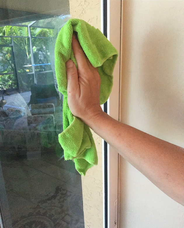 Hand with green microfiber cloth cleaning window