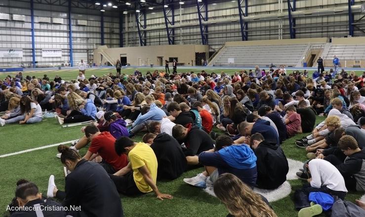 Estudiantes orando en campo deportivo de escuela
