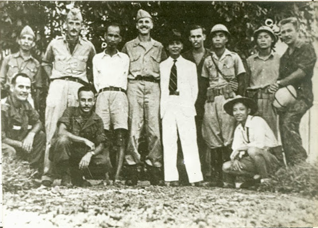 The Viet Minh and the OSS Deer team (August 1945) Standing left to right: Unidentified, Lieutenant Rene Defoumeaux, Ho Chi Minh, Major Allison K. Thomas, General Vo Nguyen Giap, Pfc Henry Prunier, Unidentified, Unidentified, and Pfc Paul Hoagland. Kneeling left to right: Lawrence Vogt, Sergeant Aaron Squires, and Unidentified.