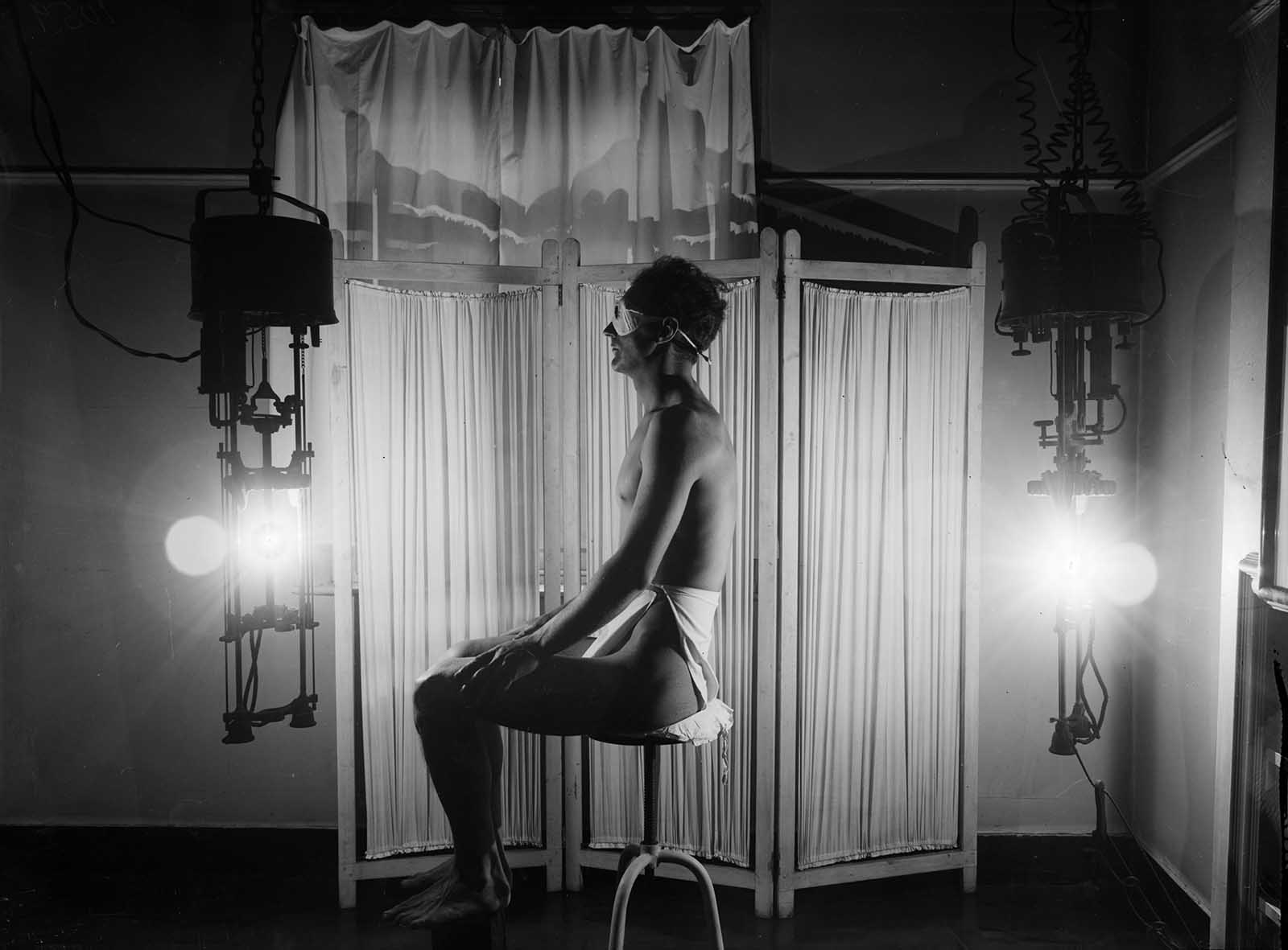 Un hombre disfruta de una lámpara de rayos solares, hacia 1930.
