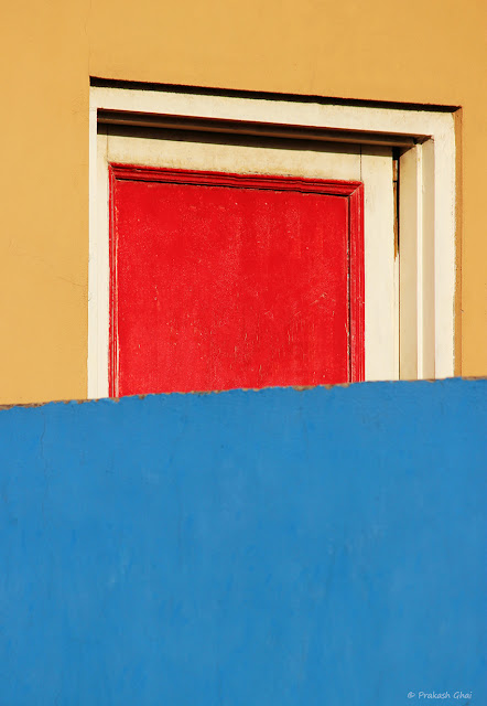 A Minimalist Photograph of a Red Door surrounded by beige and blue colored walls.