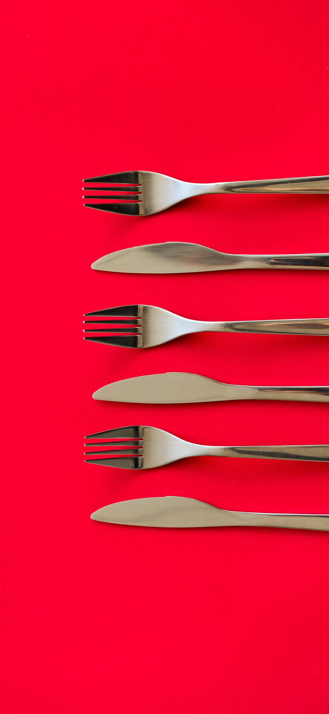 خلفية أدوات تناول الطعام فوق مائدة حمراء