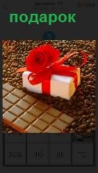 Россыпь шоколадных зерен, на которых лежит плитка шоколада и подарок в коробке, перевязанный красной лентой
