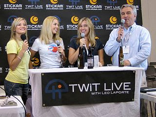 Three attractive blonds holding microphones at an exposition.