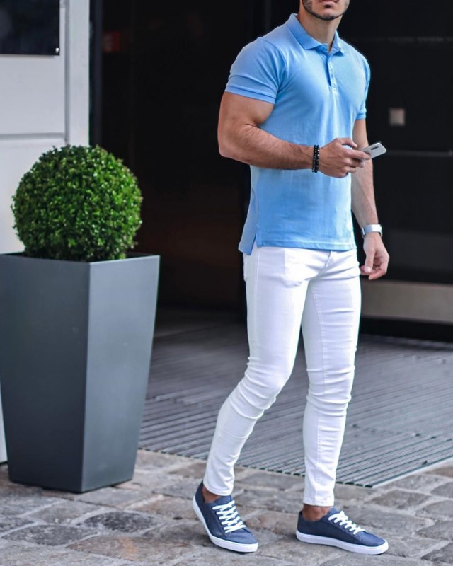A man wearing skyblue polo shirt and white jeans.