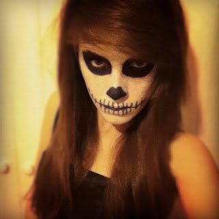 My dead ballerina makeup look, featuring another skull-like makeup look, with black eyes and skeleton nose and mouth, staring hauntingly into the camera.