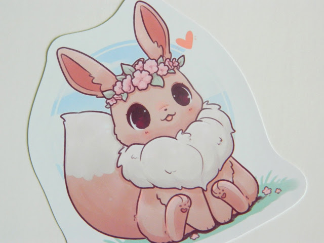 A photo of a sticker by artist Naomi Lord featuring the Pokemon Eevee wearing a flower crown