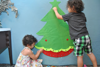 Young boy and girl decorating a felt tree that is on the wall