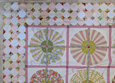 A portion of the Wheel quilt showing some of the wheels with a narrow red and white striped sashing and a border of three rows of low volume snowball blocks