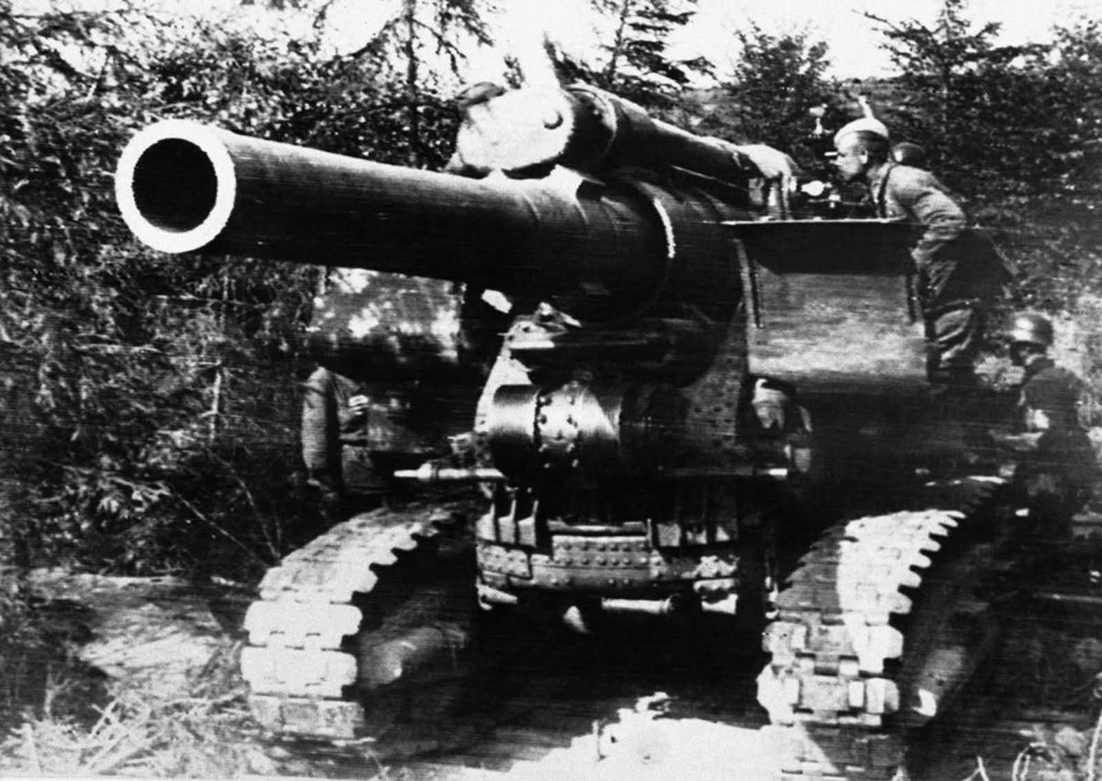 A huge Russian gun on tracks, likely a 203 mm howitzer M1931, is manned by its crew in a well-concealed position on the Russian front on September 15, 1941.