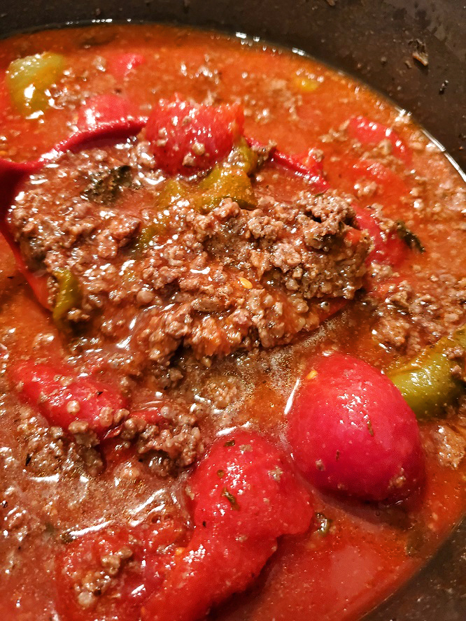 this is a bowl cast-iron dutch oven filled with chili con carne
