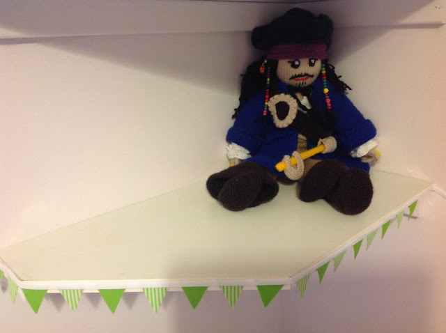knitted pirate sat on shelf with green bunting as trim
