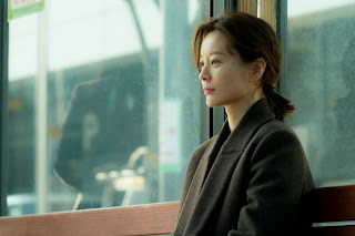 Young Korean woman in a business suit looking out of an office window.
